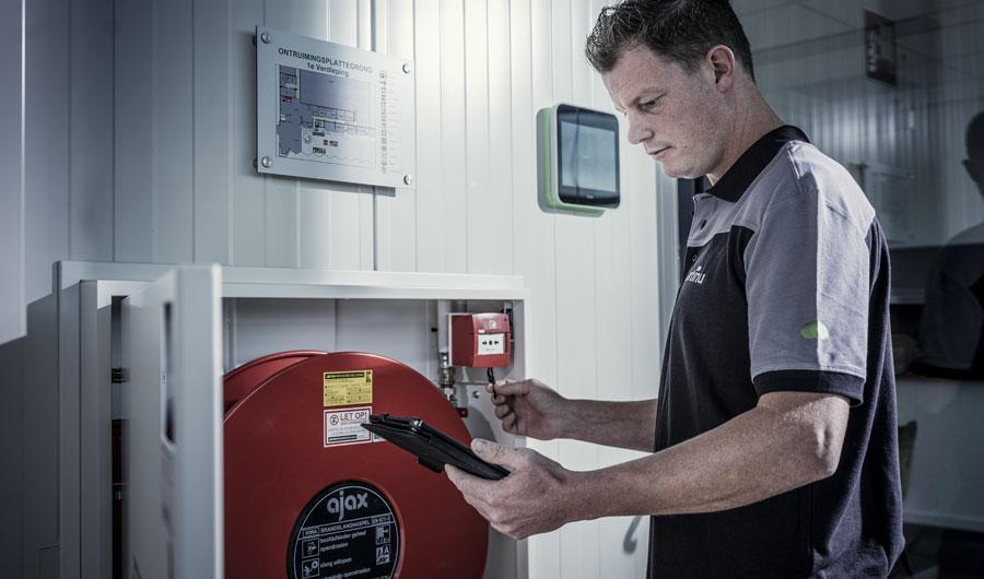 Een monteur van Martinu controleert of het brandalarm naar behoren werkt