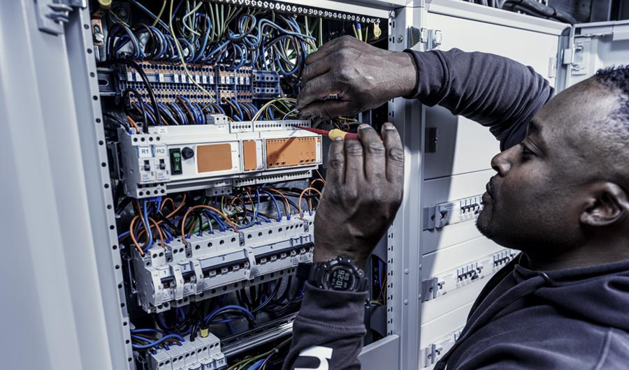 Monteur van Martinu pleegt onderhoud aan een elektrotechnische installatie