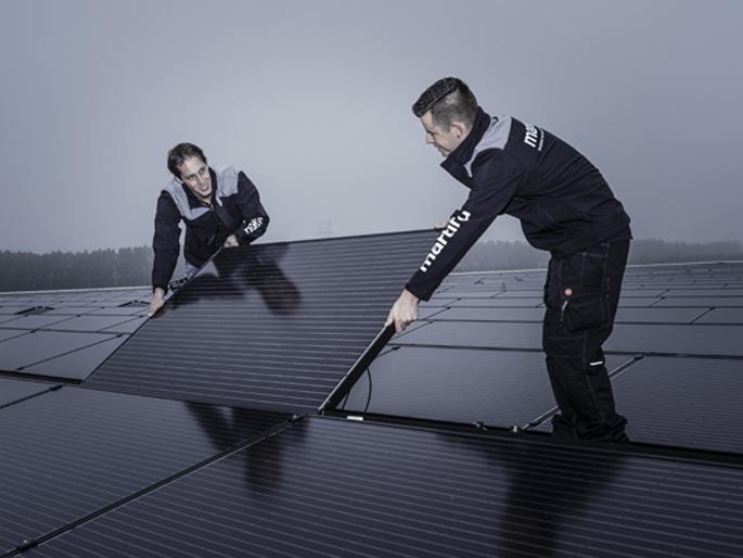 Monteurs van Martinu plaatsen zonnepanelen op het dak van een bedrijfsgebouw